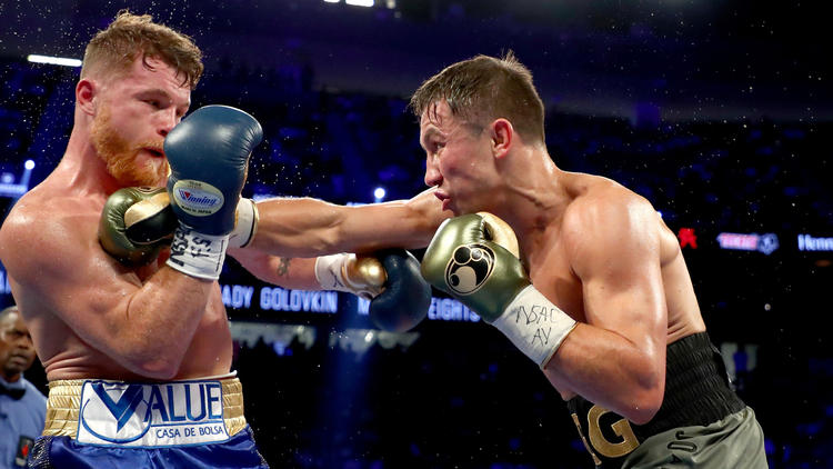 Gennady Golovkin lands a straight right to the chest of Canelo Alvarez. (Al Bello / Getty Images)