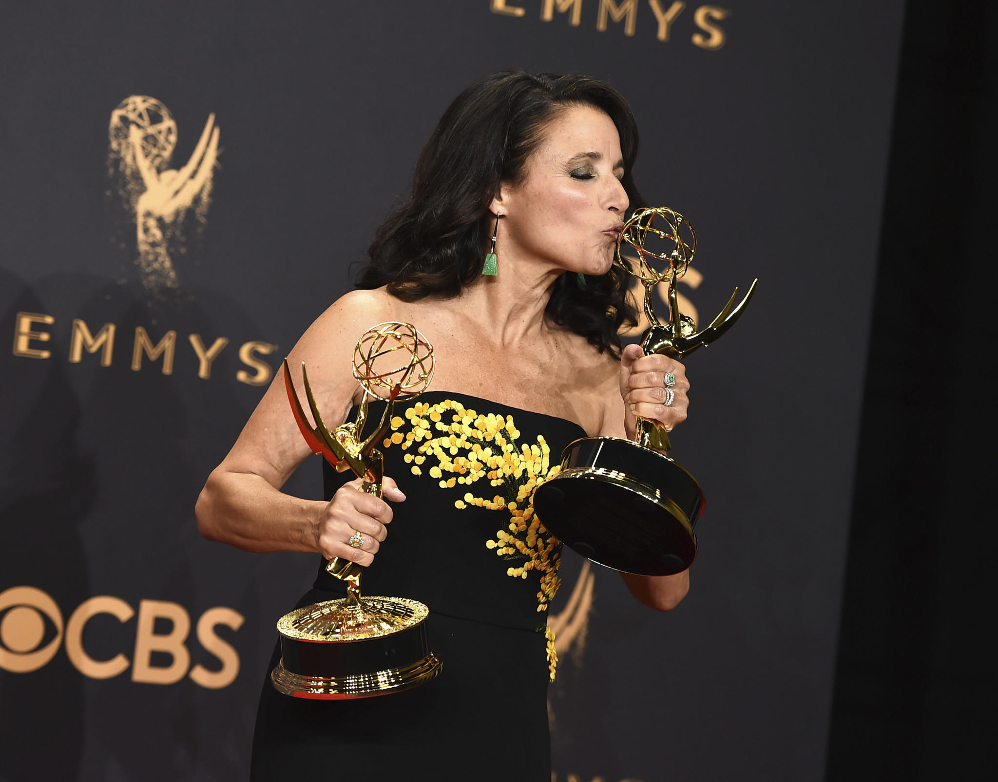 """Julia Louis-Dreyfus poses in the press room with her awards for lead actress in a comedy series and omedy series for """"Veep."""" (Jordan Strauss / Invision / AP)"""
