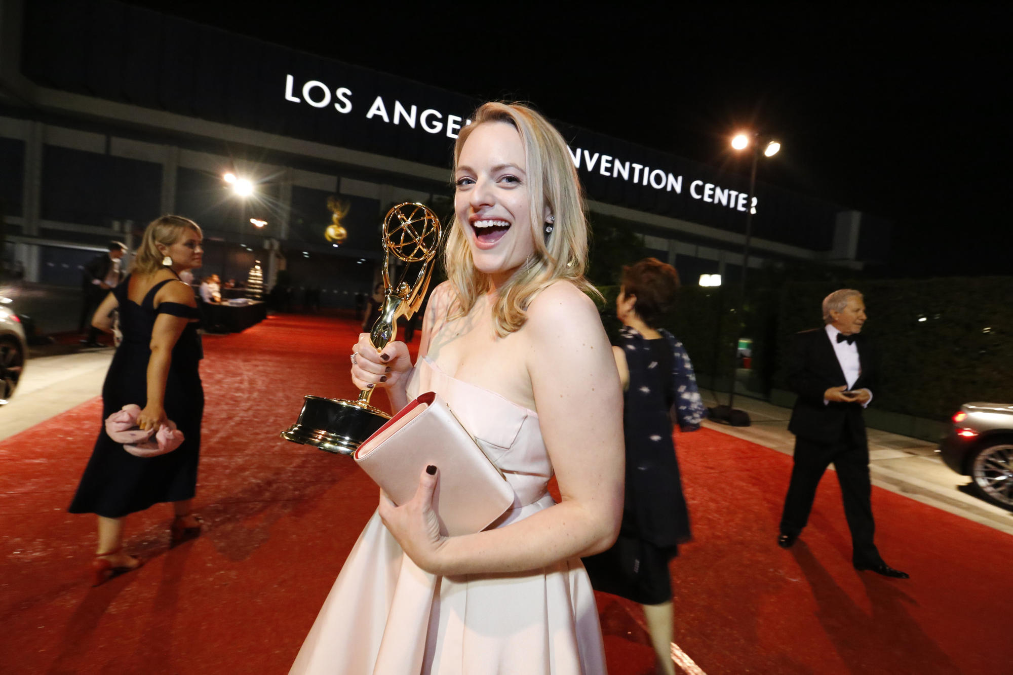 """The Handmaid's Tale's"" Elisabeth Moss holds up her Emmy Awards out side the Los Angeles Convention Center. (Al Seib / Los Angeles Times)"