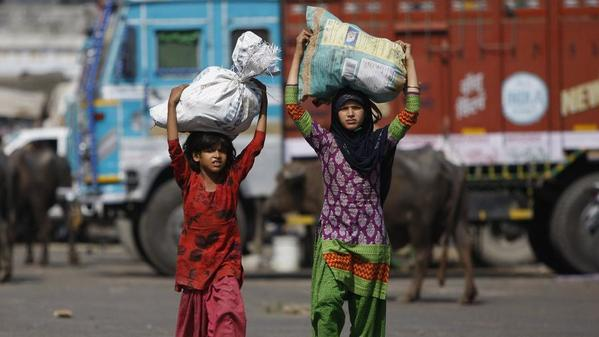 In this 2015 photo, Indian child laborers carry sacks of vegetable leftovers collected from a wholesale market to sell in their shantytown on the outskirts of Jammu, India. (Channi Anand / Associated Press)