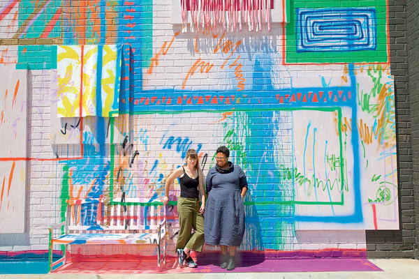 Artist Sarah Cain (left) and ICA curator Jamillah James stand by Cain's mural in the courtyard.