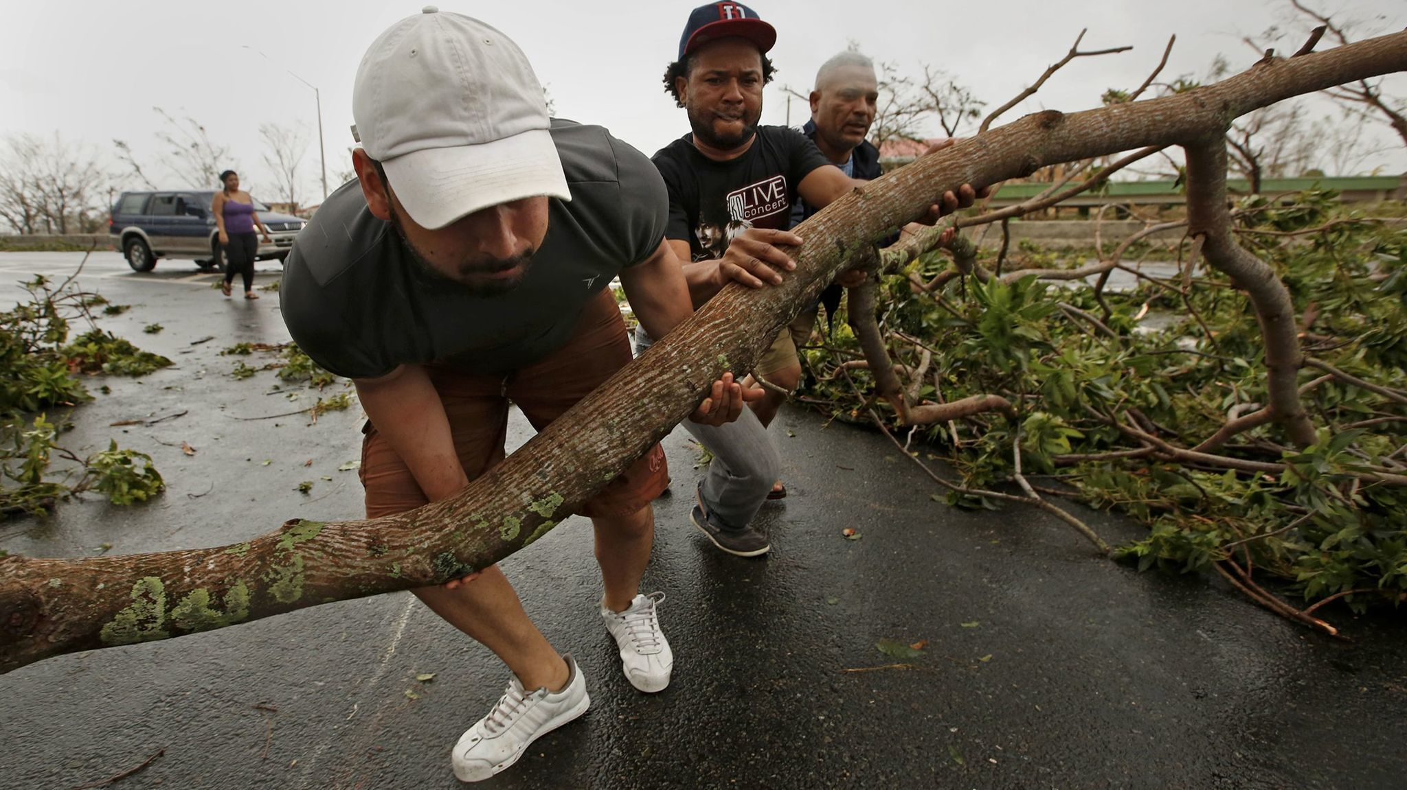 Roberto Flores, left, helps move large tree limbs from a major road in San Juan after Hurricane Maria tore through the Puerto Rican capital.