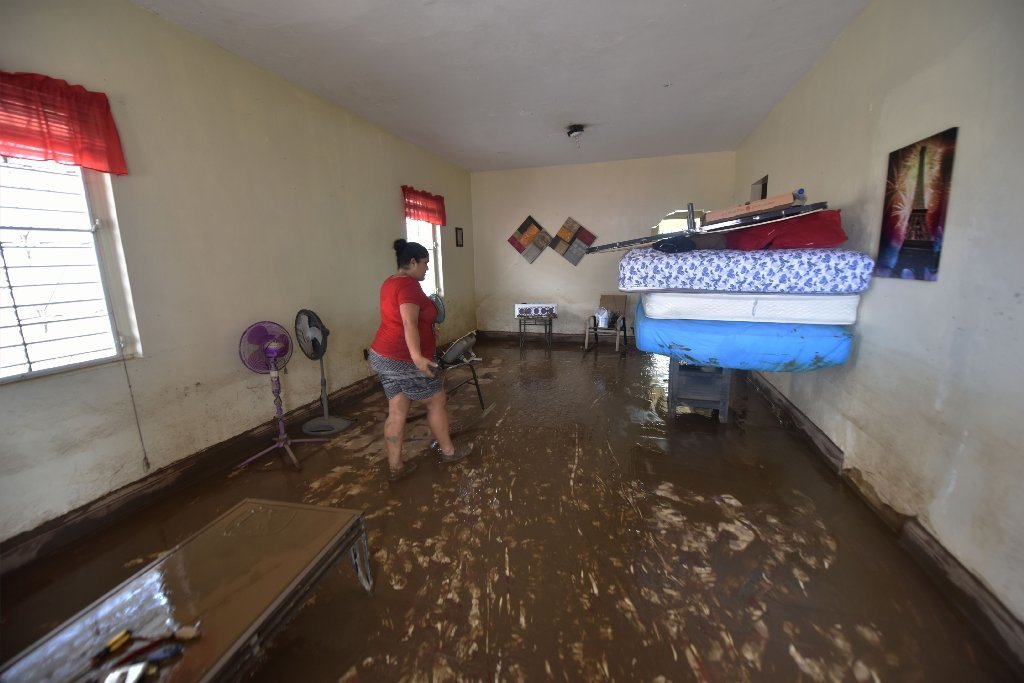 Marisabel walks inside of her house that was flooded after the passage of Hurricane Maria, in Toa Baja, Puerto Rico, on September 22, 2017.