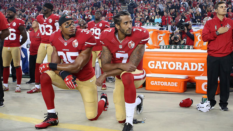 San Francisco 49ers quarterback Colin Kaepernick and Eric Reid, left, take a knee during the national anthem in a 2016 game against the Rams. (Daniel Gluskoter / Associated Press Images for Panini)