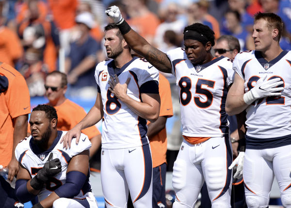 Denver Broncos tight end Virgil Green (85) gestures as teammate Max Garcia, left, takes a knee during the playing of the national anthem prior to an NFL game against the Buffalo Bills on Sept. 24.