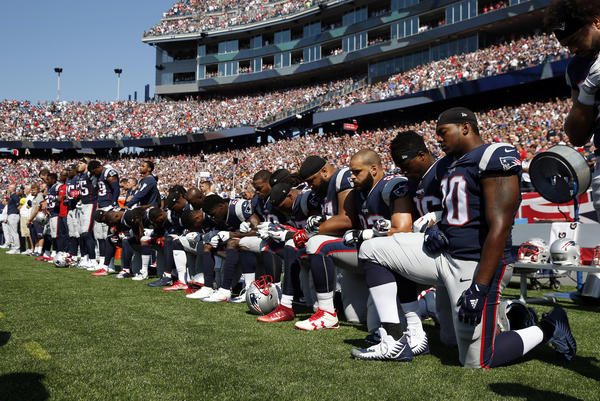 Several New England Patriots players kneel during the national anthem before a Sept. 24 game against the Houston Texans in Foxborough, Mass.