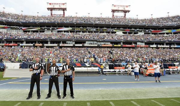 Officials stand on the sideline before a game between the Seattle Seahawks and the Tennessee Titans. Neither team came out onto the field for the anthem.