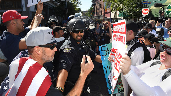 A police officer separates opposing demonstrators as they argue before a speech by Milo Yiannopoulos on Sunday at UC Berkeley.