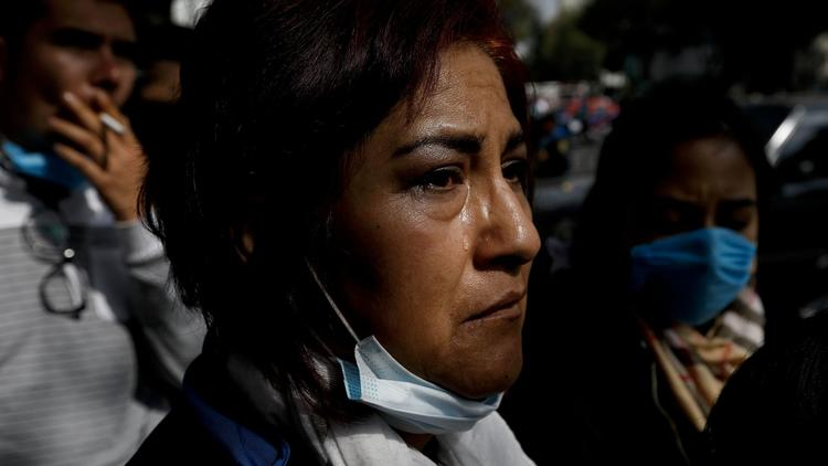 Susana Coronel Flores, whose nephew Adrian Moreno is missing in a collapsed building, sheds a tear a