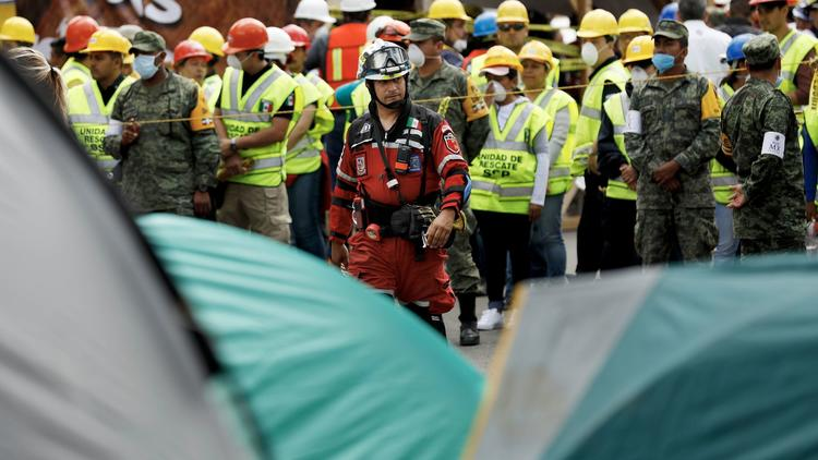 Rescuers search for victims buried under the rubble along Avenida Alvaro Obregon in Mexico City's Ro