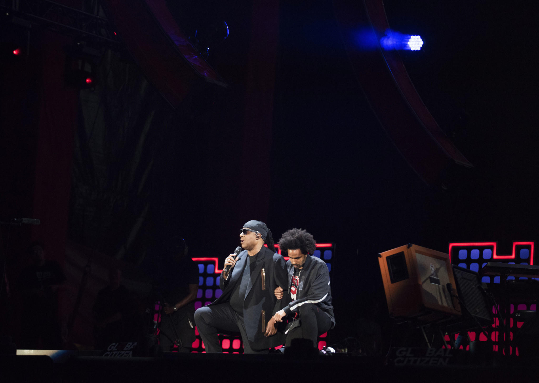 "Stevie Wonder, left, takes a knee ""for the country"" with his son, Kwame Morris, before performing at the 2017 Global Citizen Festival in New York's Central Park on Sept. 23. (Michael Noble Jr. / Associated Press)"