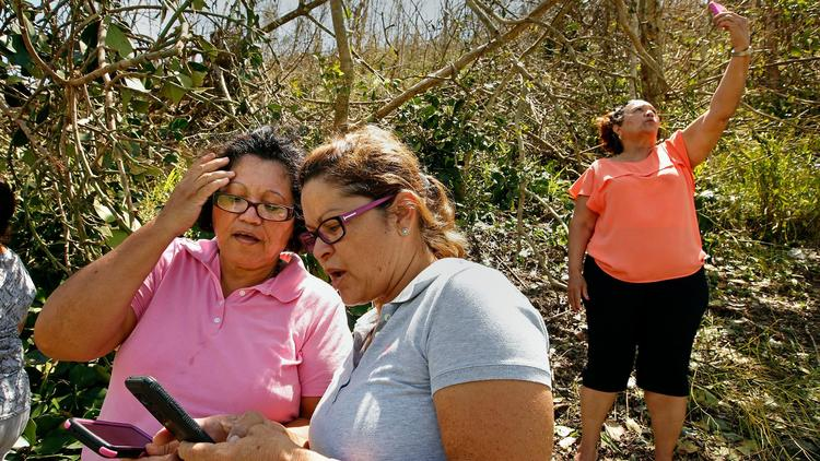 Puerto Ricans head for the island's hills to find a mobile phone signal to contact family members. (Carolyn Cole / Los Angeles Times)