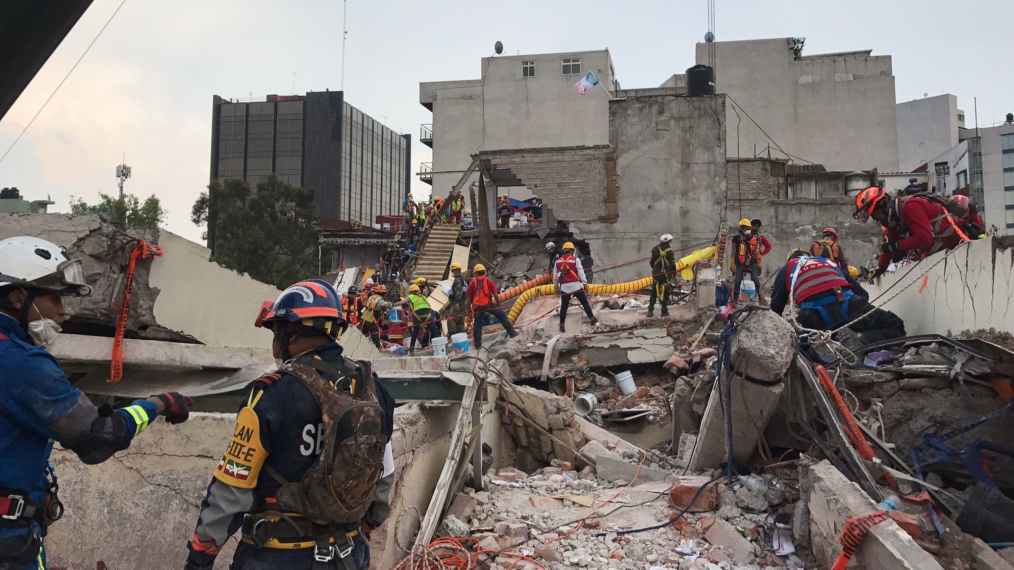 Emergency workers continue the recovery effort from the roof of the office building at Avenida Alvaro Obregon 286.