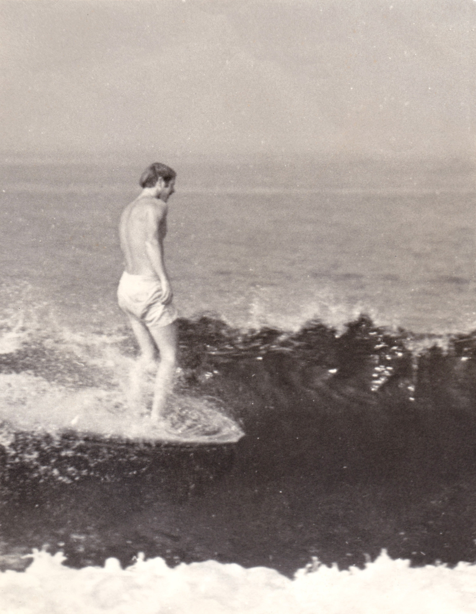 Bill Andrews rides a wave in earlier days.