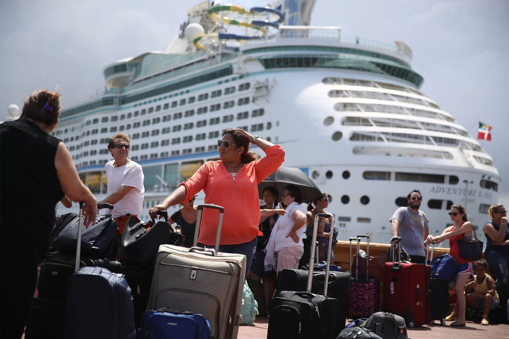 People line up to get on a Royal Caribbean International, Adventure of the Seas, relief boat that is sailing to Ft. Lauderdale, Florida with evacuees that are fleeing after the island was hit by Hurricane Maria on September 28, 2017 in San Juan, Puerto Rico.
