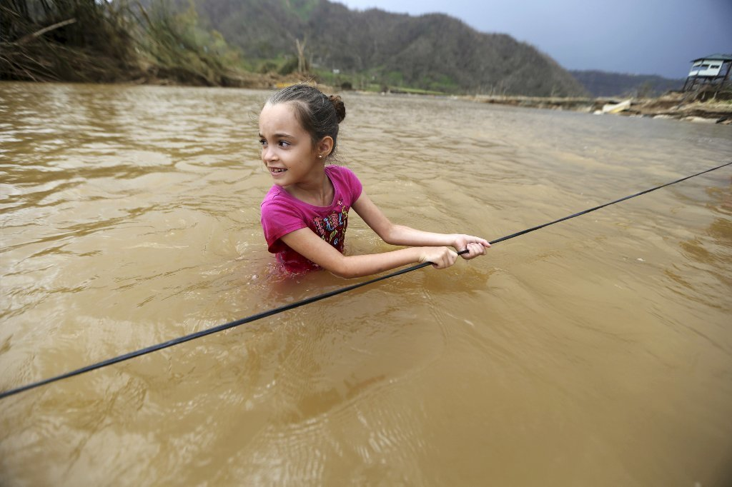 In this image of Wednesday, September 27, 2017, Ruby Rodriguez, 8, looks at her mother as she crosses the San Lorenzo Morovis River with her family, after the bridge was swept by Hurricane Maria in Morovis, Puerto Rich.