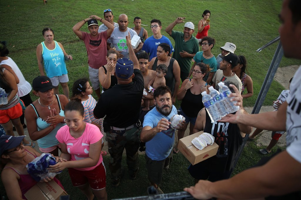 Hurricane survivors receive food and water being given out by volunteers and municipal police as they deal with the aftermath of Hurricane Maria on Sept. 28, 2017 in Toa Baja, Puerto Rico.