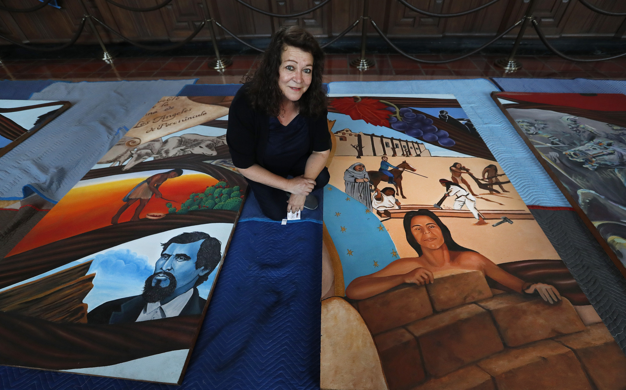 "Barbara Carrasco kneels with two sections of her 43-panel mural, ""L.A. History: A Mexican Perspective (1981)."""