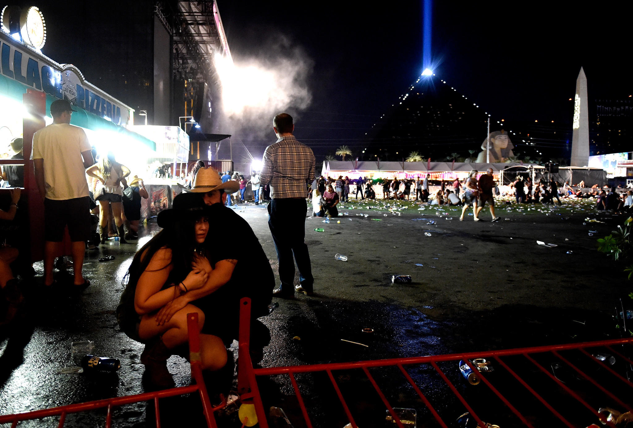 People take cover at the Route 91 Harvest country music festival in Las Vegas on Oct. 1 after gunfire was heard. (David Becker / Getty Images)