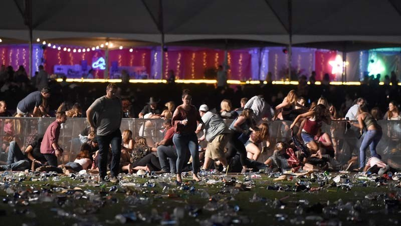 Concert-goers flee as gunfire from across the street hits the Route 91 Harvest festival at Las Vegas Village on Sunday. (David Becker / Getty Images)