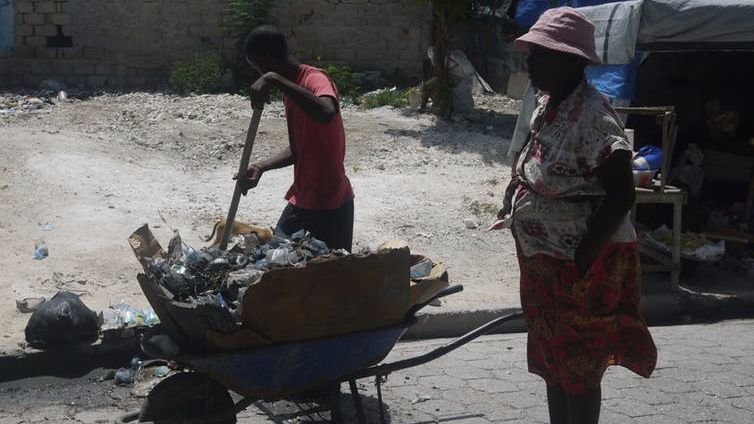 A woman and a boy collect plastic trash in a street in Port-au-Prince, Haiti.