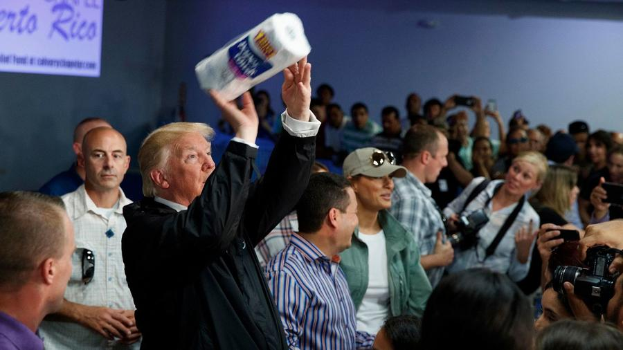 President Donald Trump tosses paper towels into a crowd like a basketball player taking a shot, at Calvary Chapel in Guaynabo, Puerto Rico on October 3rd. — Photograph: Evan Vucci/Associated Press.