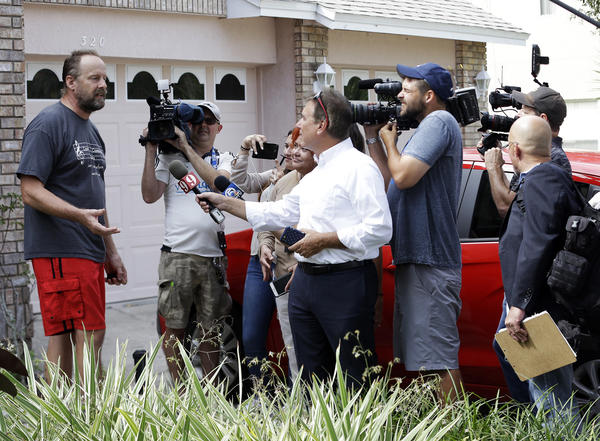 Eric Paddock, left, brother of Las Vegas gunman Stephen Paddock, speaks to members of the media outside his home Monday in Orlando, Fla. (John Raoux / Associated Press)