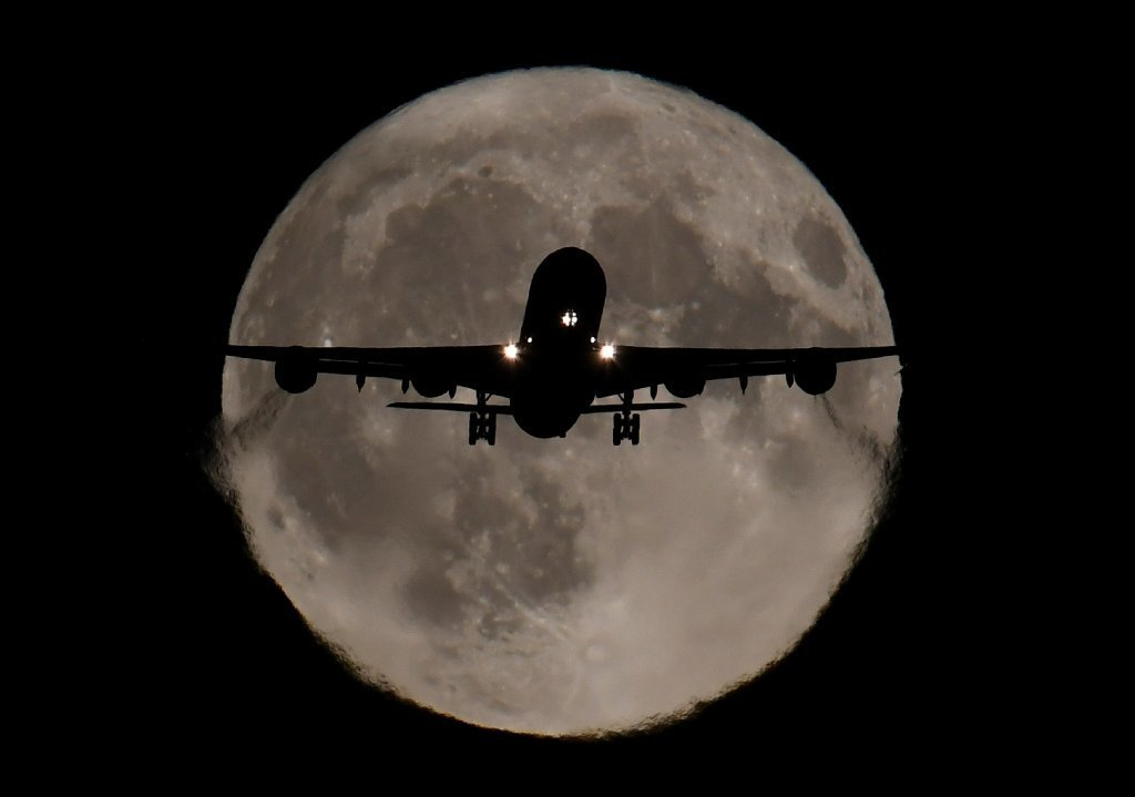 A passenger plane, with a full Harvest moon seen behind, makes its final landing approach towards Heathrow Airport in London, Britain, October 5, 2017.