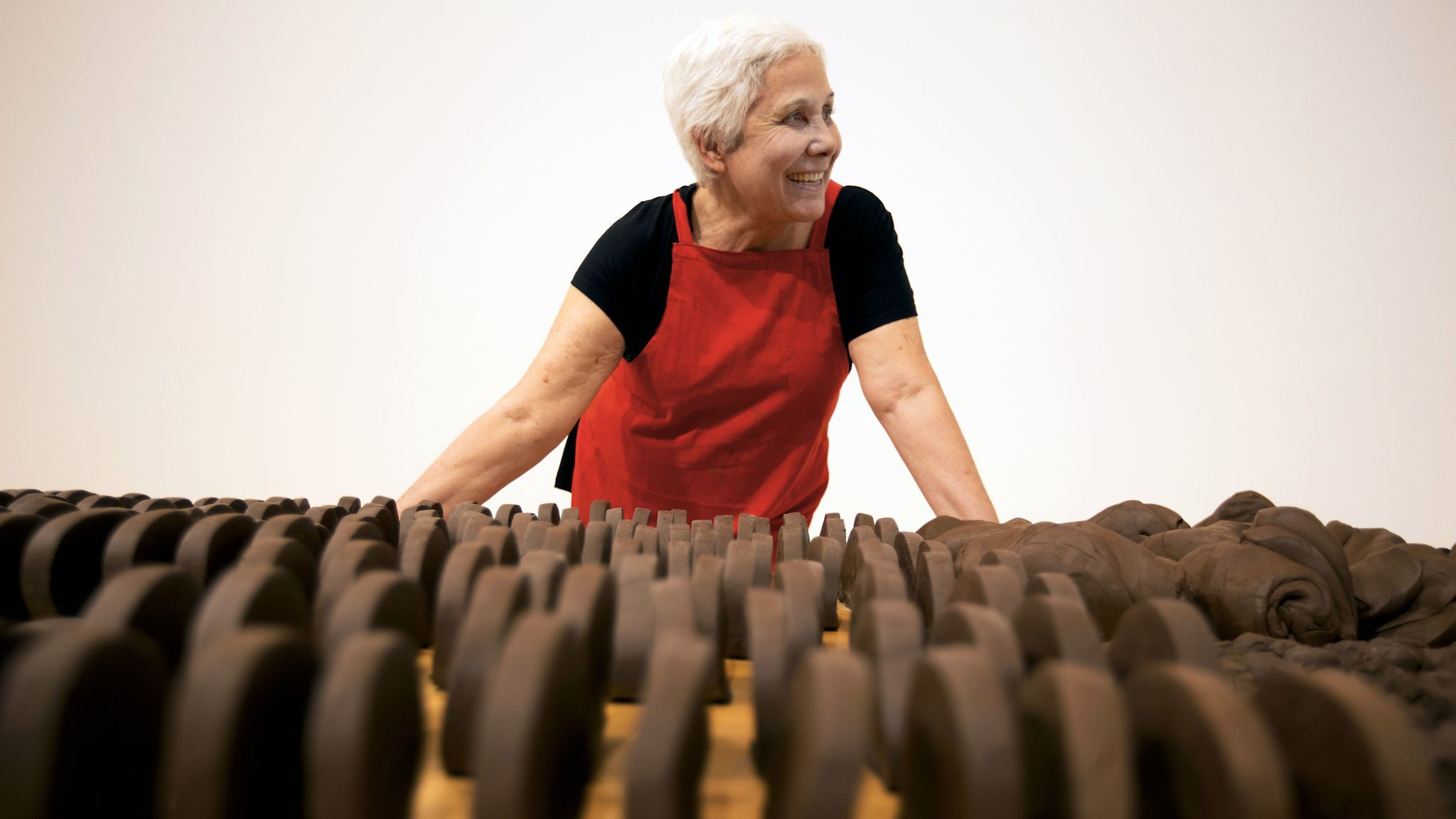 Anna Maria Maiolino stands before unfired clay objects that are part of her MOCA retrospective.