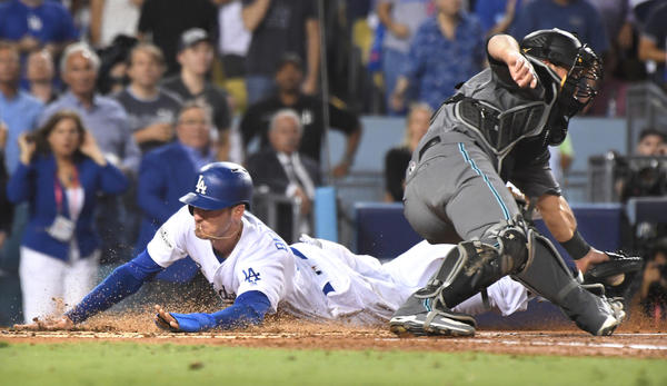 Dodgers first baseman Cody Bellinger beats the throw to Diamondbacks catcher Jeff Mathis on a double by Yasiel Puig in the first inning of Game 1 of the NLDS at Dodger Stadium. (Wally Skalij / Los Angeles Times)