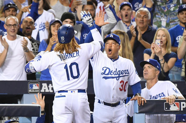 Dodgers third baseman Justin Turner celebrates his three-run home run against the Diamondbacks with manager Dave Roberts in the first inning in Game 1 of the NLDS at Dodger Stadium. (Wally Skalij / Los Angeles Times)