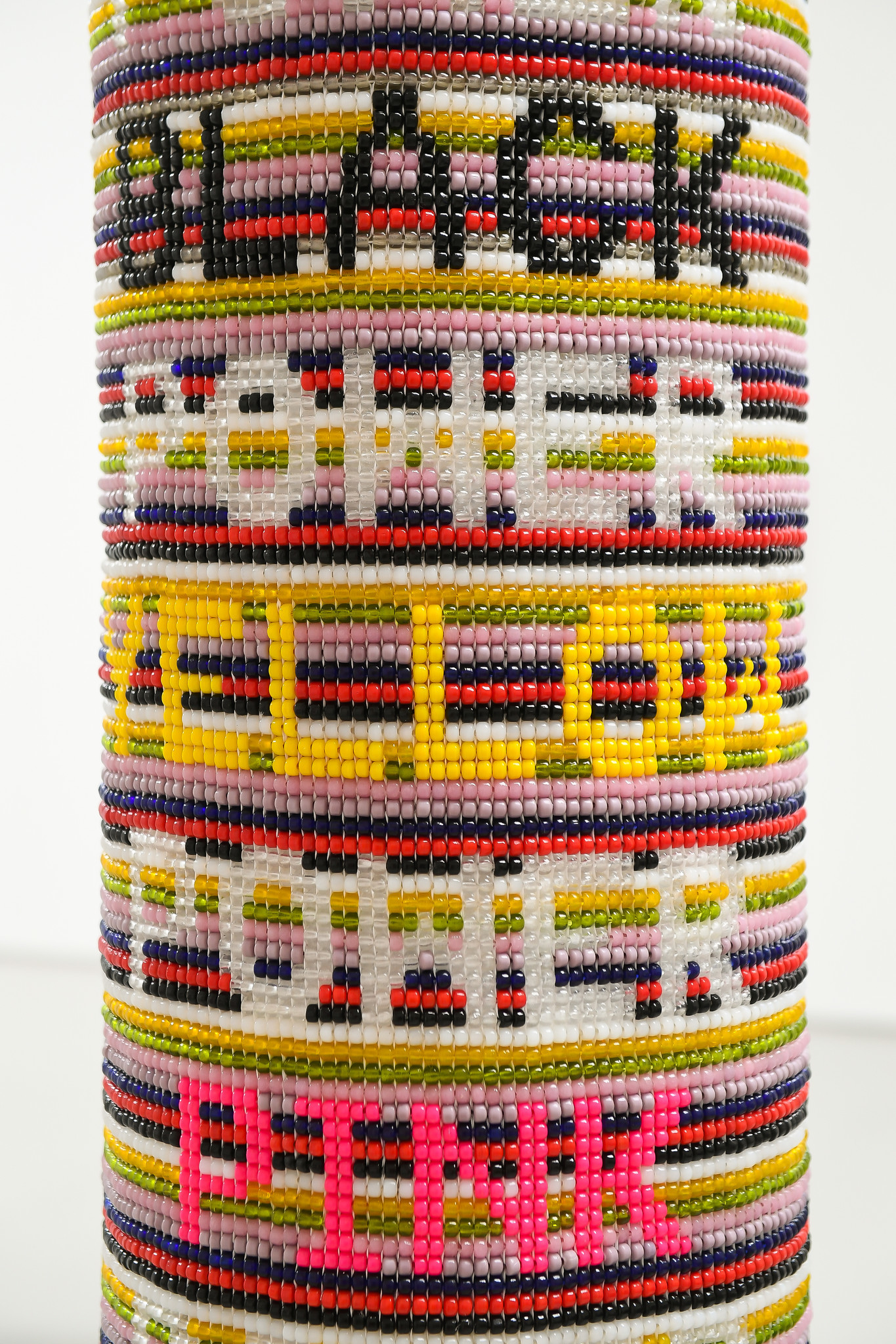 "Detail of Jeffrey Gibson's ""Power Power Power."" The full piece reads, ""black power yellow power pink power blue power."" 2017, repurposed vinyl punching bag, glass beads, artificial sinew, acrylic felt. 51 inches by 12 inches."