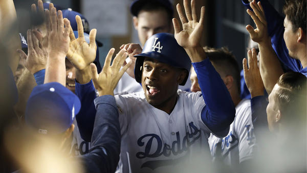 Curtis Granderson high-fives in the dugout after scoring on a 2-run double on a hit by Austin Barnes in the 5th inning. (Gina Ferazzi / Los Angeles Times)