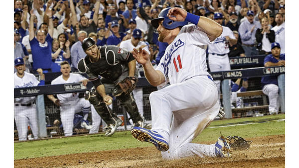 Dodgers second baseman Logan Forsythe scores on a wild pitch by DBacks pitcher Robbie Ray