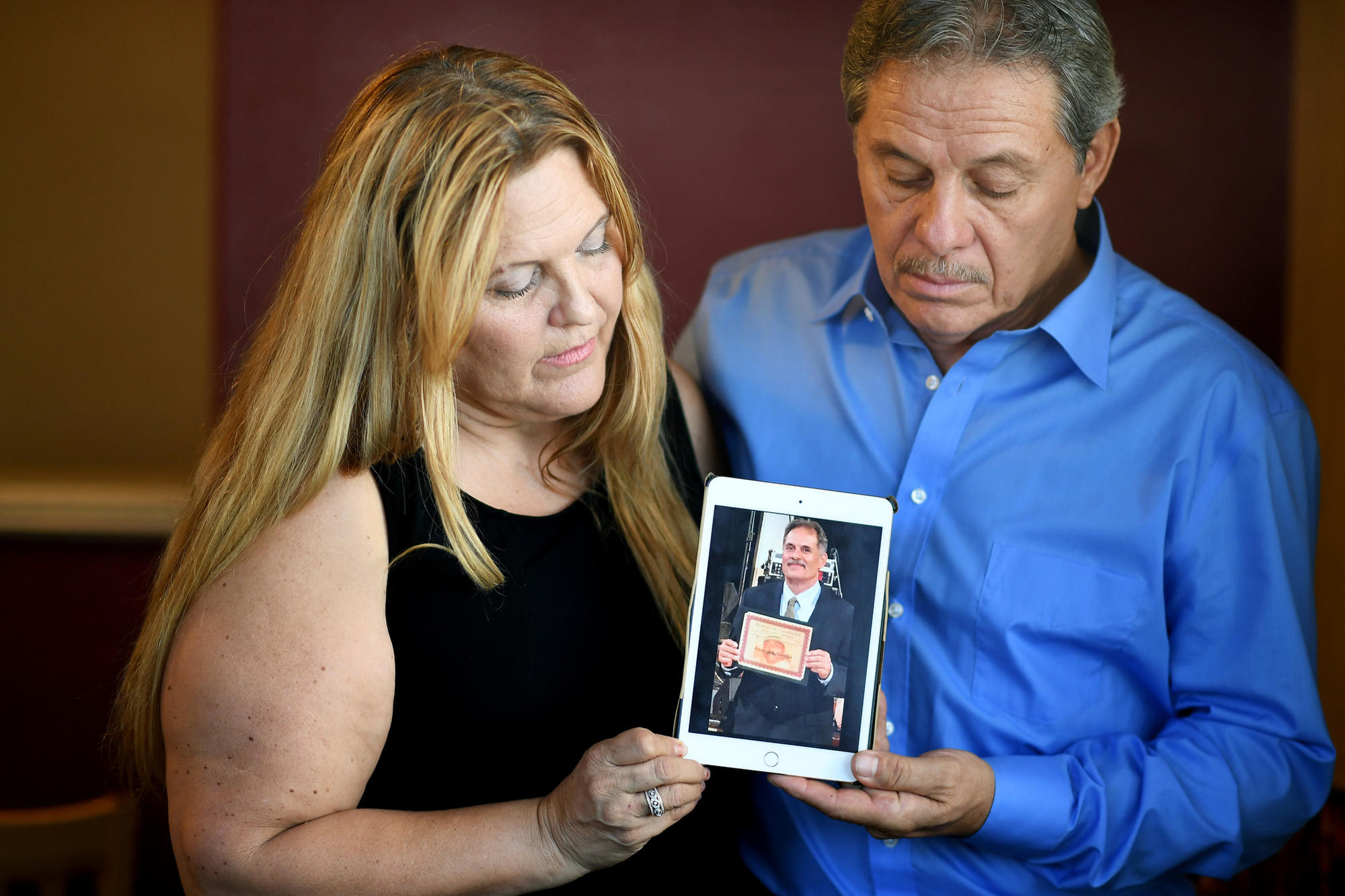 Carmelita Vargas, left, and Arturo Garcia hold a photo of their brother Arnulfo Garcia.