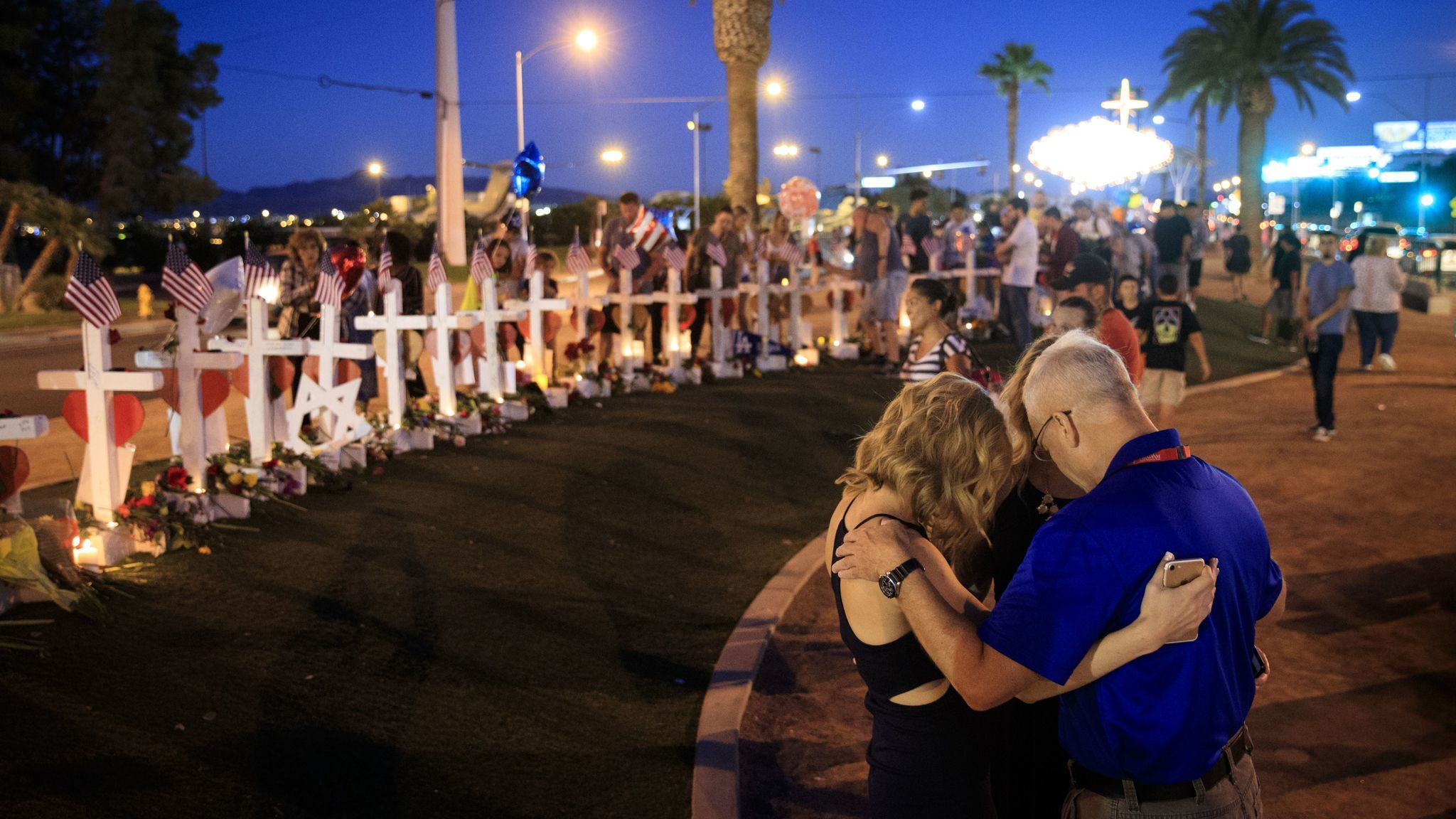Some visitors pay at the temporary memorial with 58 white crosses, one for each victim, on the south end of Las Vegas Strip,