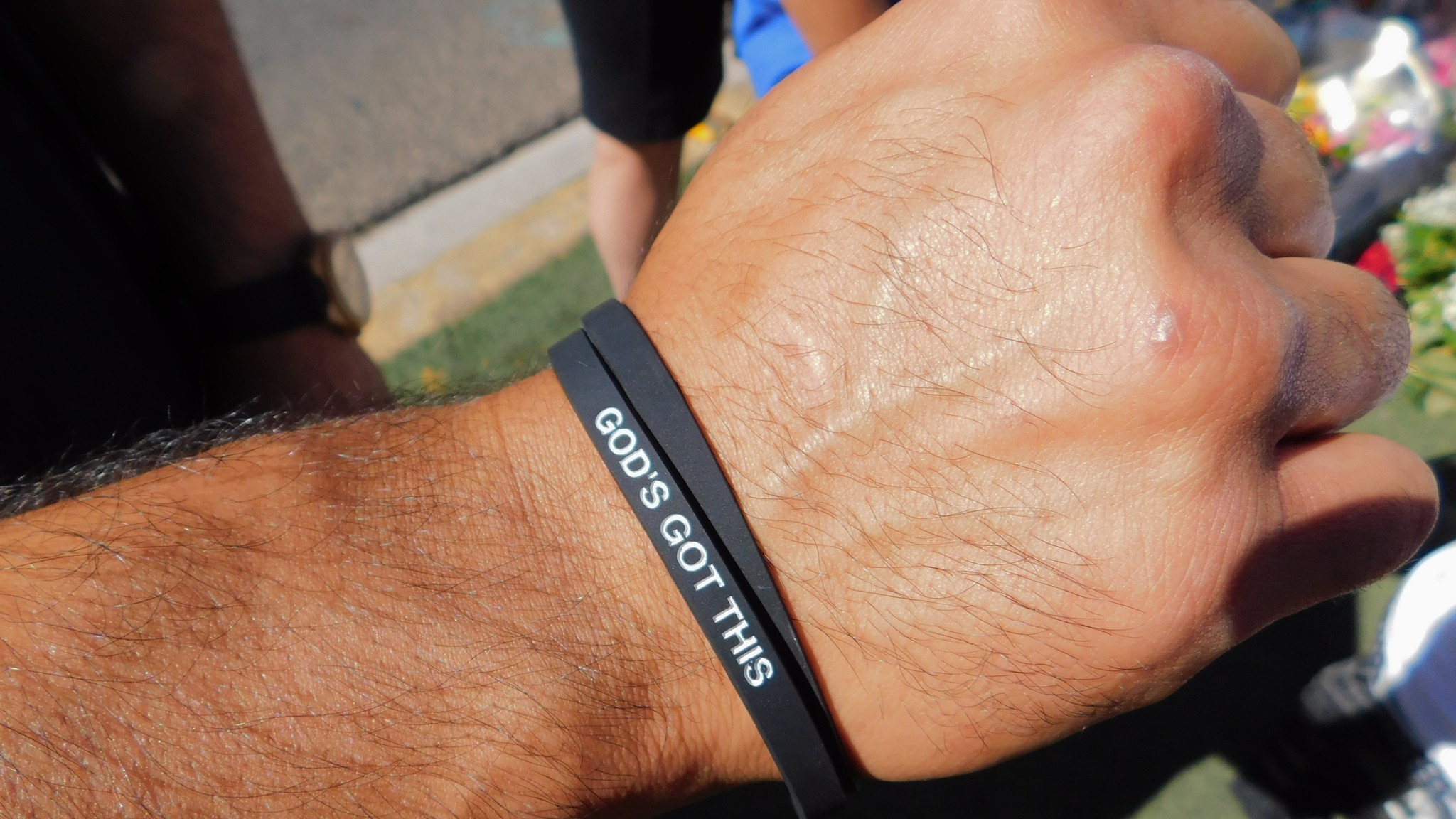 """Brian Cordero of Chino on Oct. 7 handed out rubber wristbands in Las Vegas bearing the words """"God's Got This."""""""
