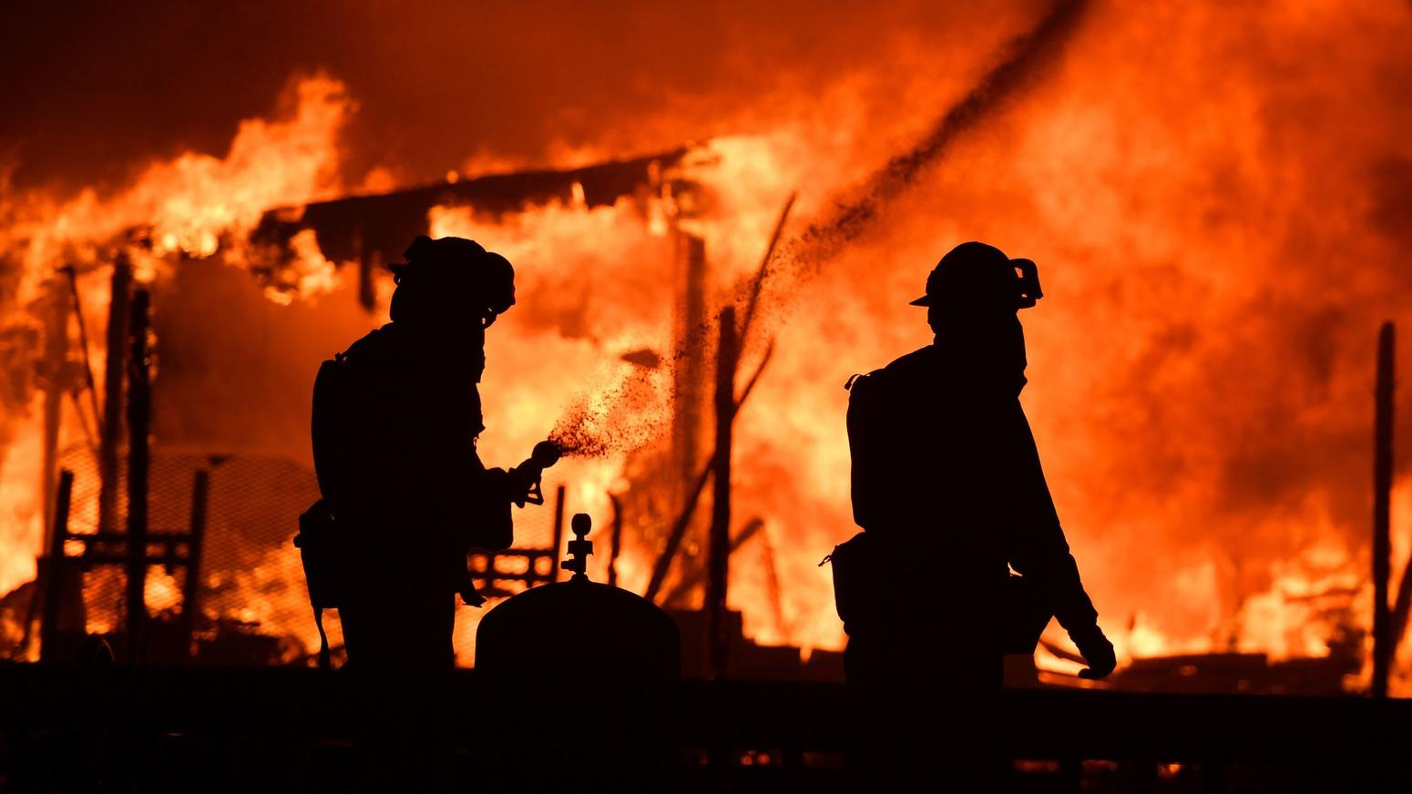 Firefighters douse flames as a home burns in the Napa wine region, as multiple wind-driven fires continue to whip through the region. (Josh Edelson / AFP/Getty Images)