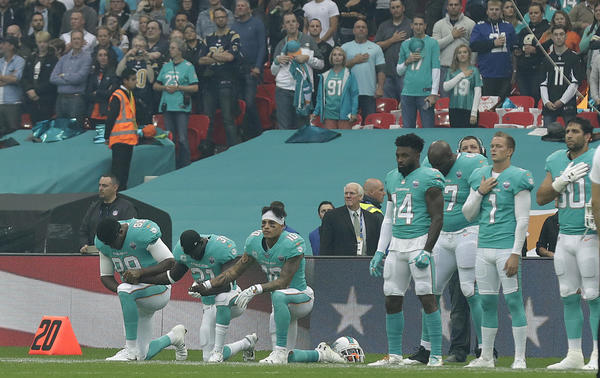 Miami Dolphins' Julius Thomas (89), Michael Thomas (31) and Kenny Stills take a knee as the national anthem is played before their game against the New Orleans Saints in London on Oct. 1. (Matt Dunham / Associated Press)