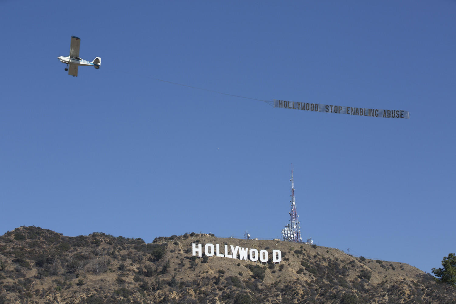 """A banner reading """"Hollywood: Stop Enabling Abuse"""" flew over the Hollywood sign on Tuesday in the wake of a slew of sexual harassment accusations against movie producer Harvey Weinstein. (Ray Ampudia / UltraViolet)"""
