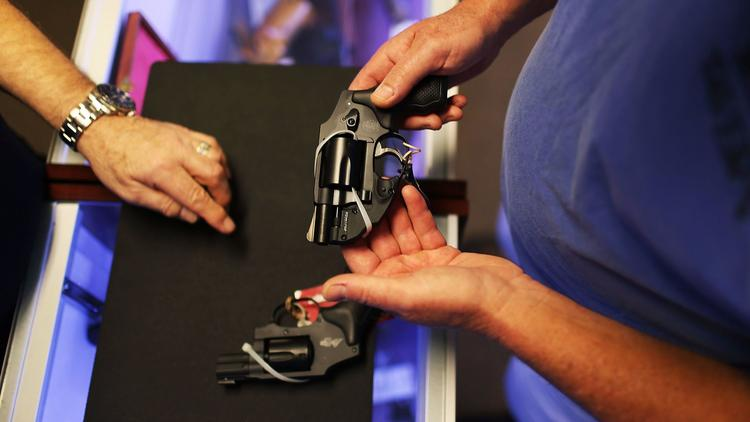 A customer shops for a handgun, which will be banned from California school campuses. (Joe Raedle / Getty Images)