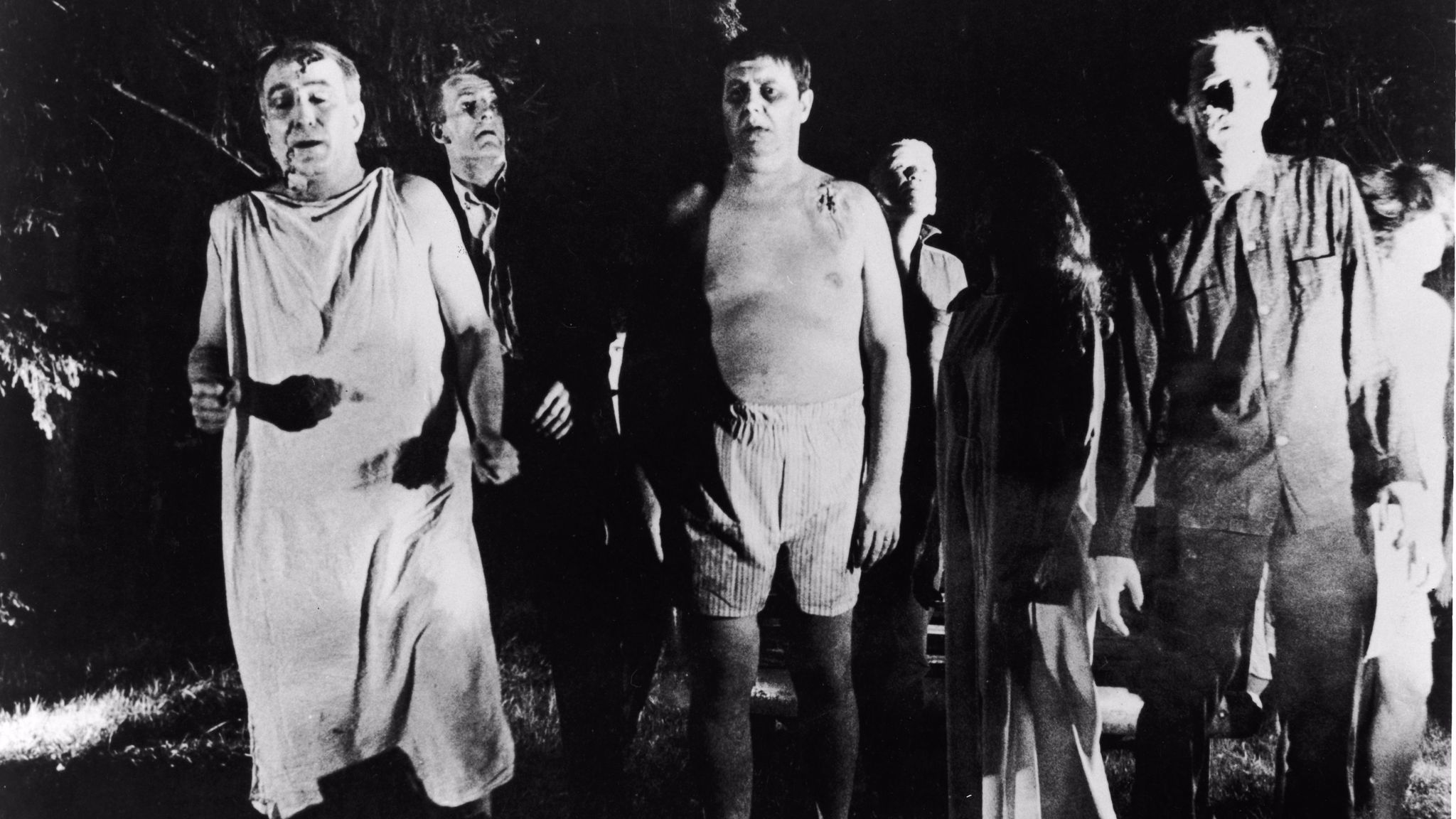 "A line of undead 'zombies' walk through a field in ""Night Of The Living Dead."""