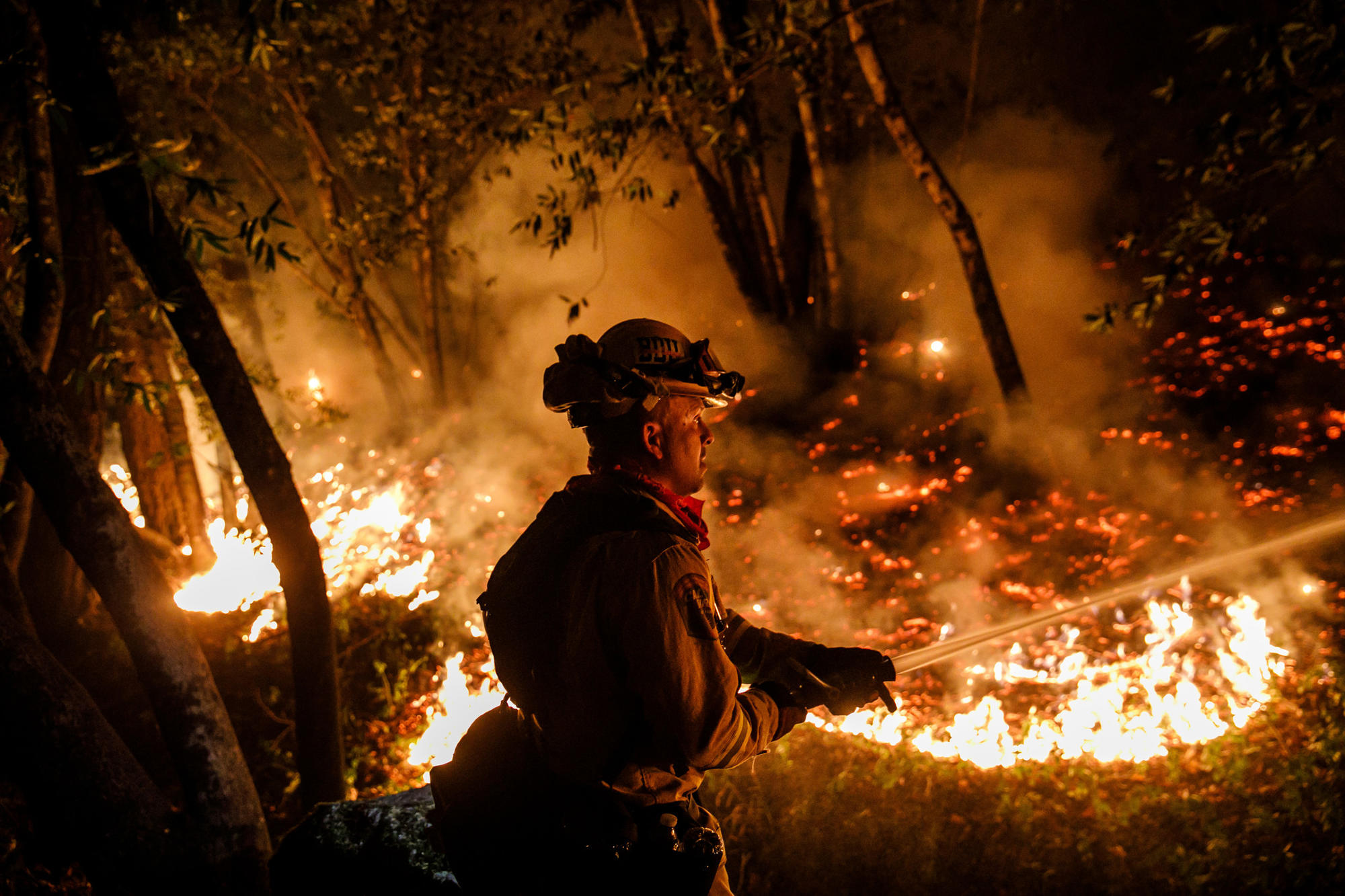 Firefighter Mario Topete attacks flames as his unit tries to prevent a fire from crossing Highway 29 north of Calistoga on Oct. 12.