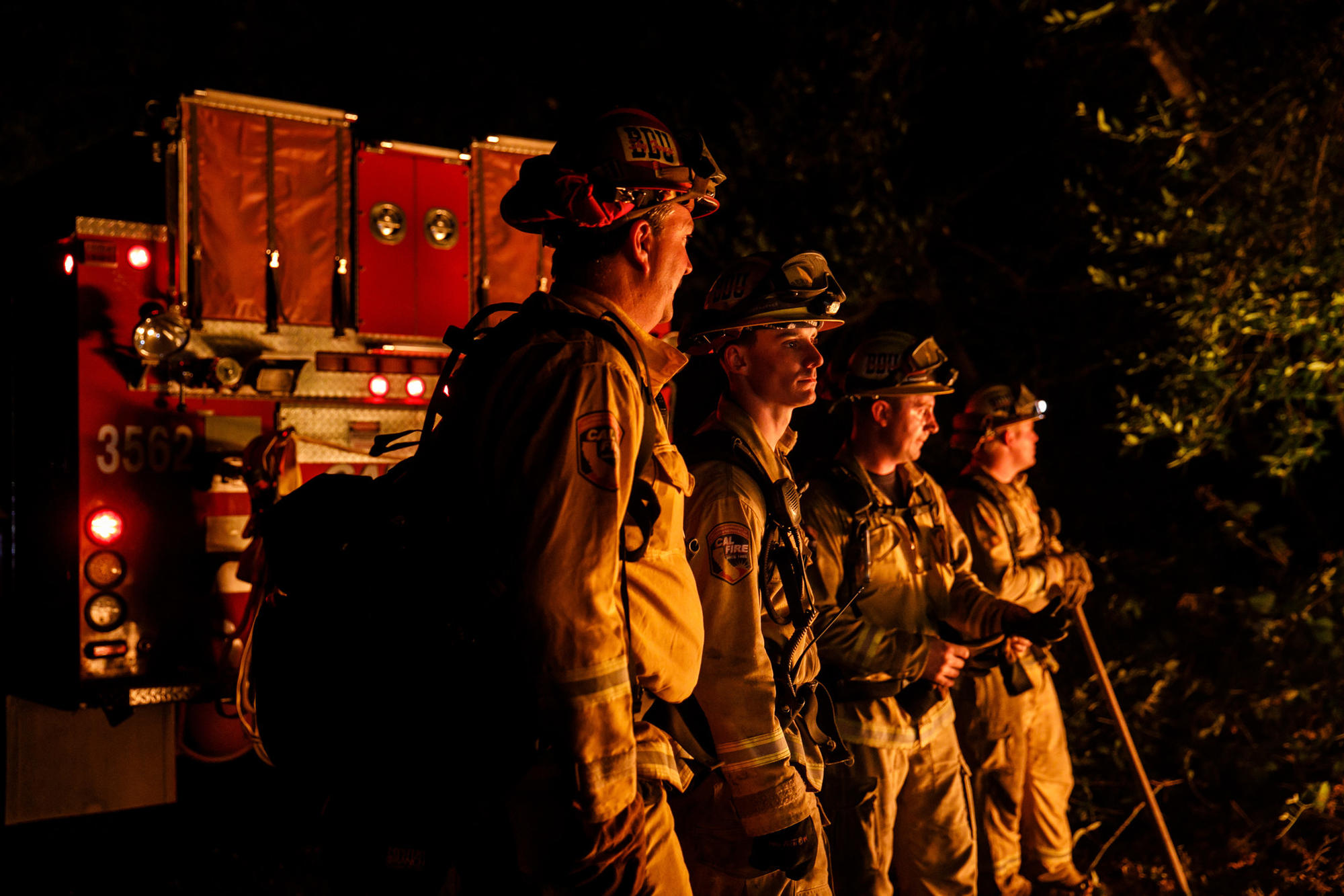 From left, firefighters Gary Mattingly, Tim Zanotelli, Brandon Tolp and Devon Elenburg, all based in San Bernardino, stand ready to swing into action along Highway 29 north of Calistoga on Oct. 12.