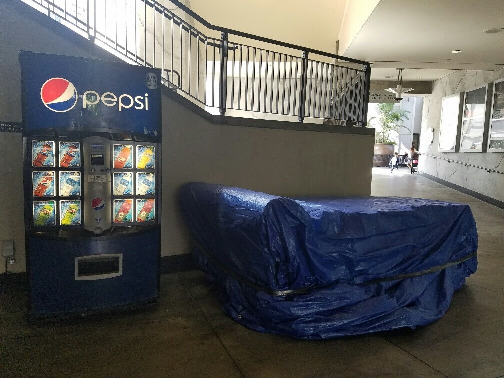 The censored daybed sculpture is being stored nearby under a blue tarp.