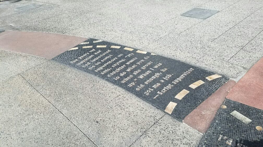 Mosaic texts that tell stories of men and women who came to work in Hollywood are embedded in the pavement.