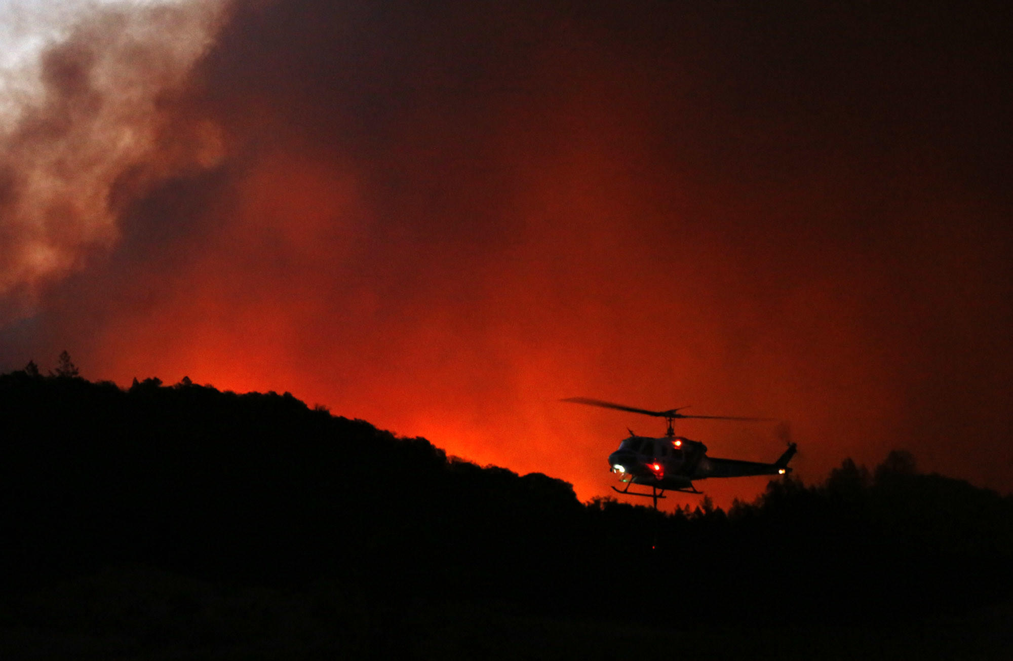 A helicopter prepares to drop water on a fire threatening the Oakmont community along Highway 12 in Santa Rosa on Oct. 13.