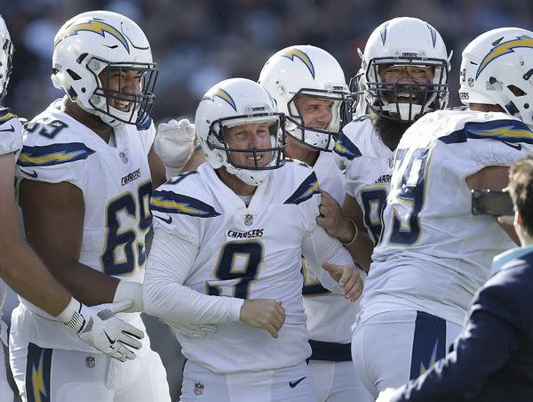 Chargers kicker Nick Novak is surrounded by his teammates after making a 32-yard field goal to beat the Oakland Raiders as time expired. (Ben Margot / Associated Press)