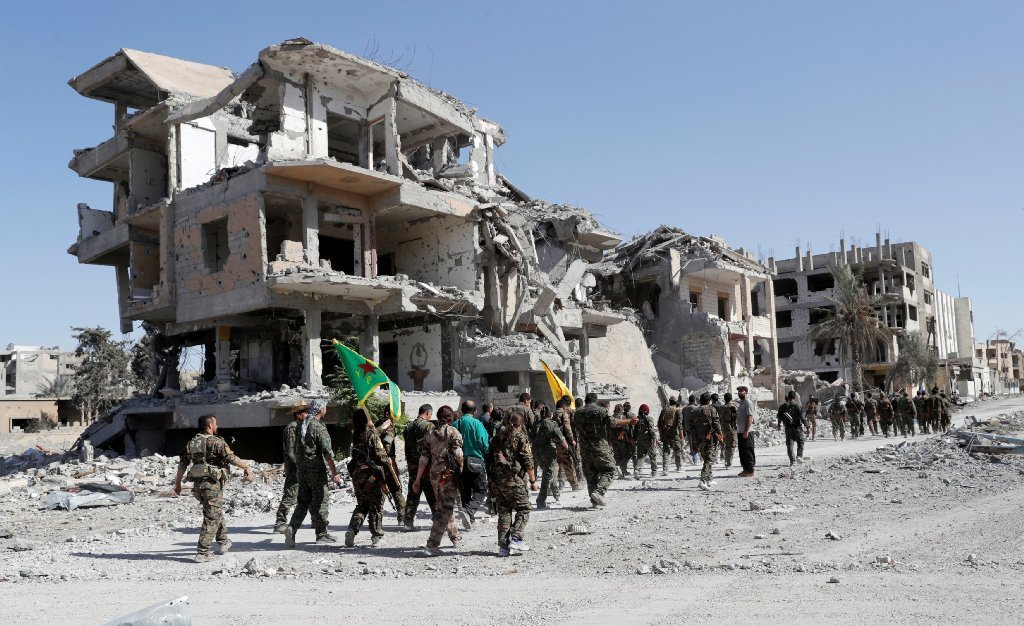 Fighters of Syrian Democratic Forces (SDF) march past destroyed buildings as they celebrate victory and liberation of Raqqa from the Islamic State militants, in Raqqa, Syria, October 17, 2017.