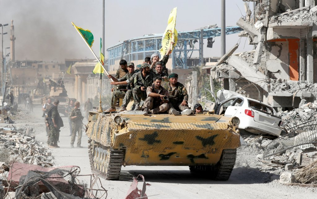 Syrian Democratic Forces (SDF) fighters ride atop of military vehicle as they celebrate victory in Raqqa, Syria, October 17, 2017.